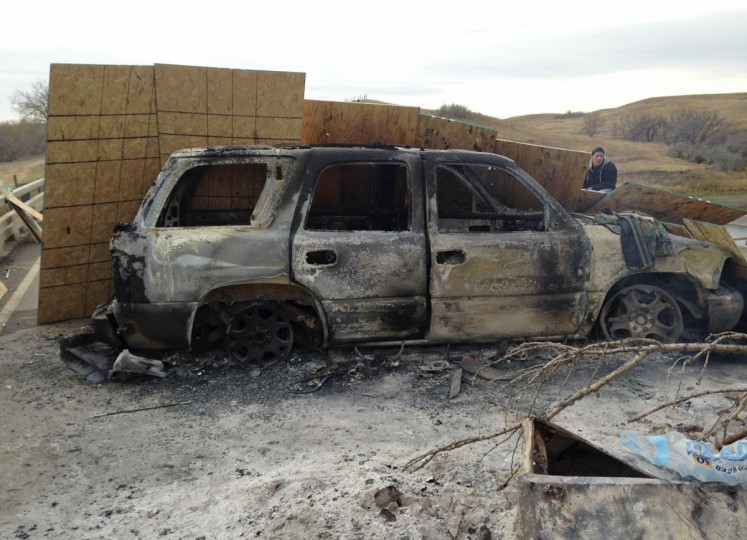 A burned-out truck sits on Highway 1806 near Cannon Ball, N.D., on Friday, Oct. 28, near the spot where protesters of the Dakota Access pipeline were evicted from private property a day earlier. Authorities say protesters burned several pieces of construction equipment and other vehicles Thursday during a chaotic confrontation with law enforcement. (AP Photo/James MacPherson)