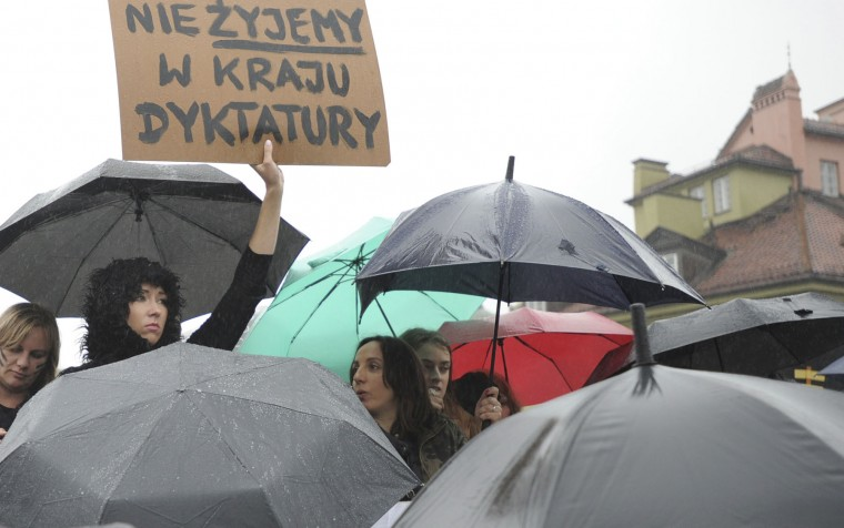 "Women gather at the Castle Square in a nationwide ""Black Monday"" strike to protest a legislative proposal for a total ban on abortion, in Warsaw, Poland, Monday, Oct. 3, 2016. Massive protests were held in the rain in the streets of Warsaw, Gdansk, Wroclaw and elsewhere across the largely Catholic nation led by a conservative government. The placard reads: We don't live in a dictatorship country. (AP Photo/Alik Keplicz)"