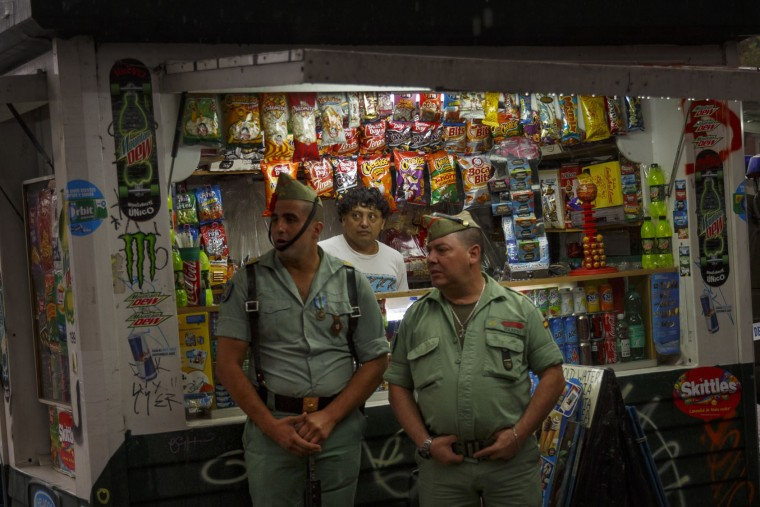 Members of La Legion, an elite unit of the Spanish Army, stand in front of a street store as they wait for the start of a military parade to celebrate a holiday known as 'Dia de la Hispanidad' or Hispanic Day in Madrid, Wednesday, Oct. 12, 2016. Almost a year into Spain's political deadlock, the country is celebrating its National Day with a military parade of over 3,000 soldiers marching through Madrid and aircraft drawing trails of red and yellow smoke in the sky to represent the flag. (AP Photo/Daniel Ochoa de Olza)