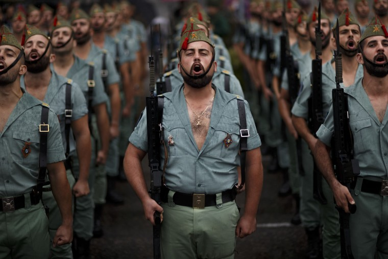 Members of La Legion, an elite unit of the Spanish Army, sing during a military parade as they celebrate a holiday known as 'Dia de la Hispanidad' or Hispanic Day in Madrid, Wednesday, Oct. 12, 2016. Almost a year into Spain's political deadlock, the country is celebrating its National Day with a military parade of over 3,000 soldiers marching through Madrid and aircraft drawing trails of red and yellow smoke in the sky to represent the flag. (AP Photo/Daniel Ochoa de Olza)