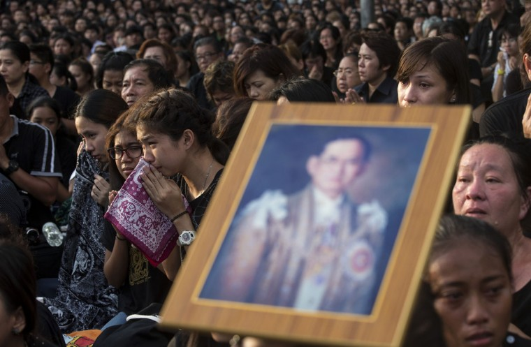 Thais sob as they wait to pay their last respects to the body of King Bhumibol Adulyadej on the ground outside Grand Palace in a royal procession led by son and heir apparent Crown Prince Vajiralongkorn in Bangkok, Thailand Friday, Oct. 14, 2016. Bhumibol, the world's longest reigning monarch, died on Thursday at the age of 88. (AP Photo/Wason Wanichakorn)