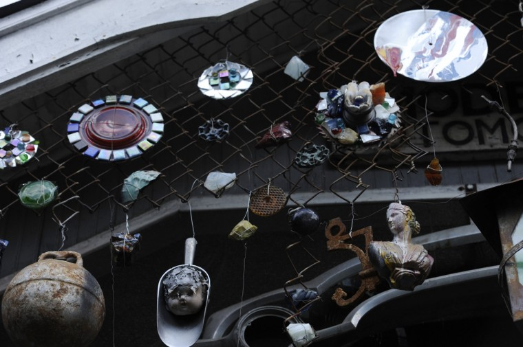 "Pieces of glass, figures, and other objects hang from chain link fencing attached to a gable outside Artist A. Clarke Bedford's home he has named ""As-sem-blage Co-ttage, ""  pronounced in rhyming French. (Kim Hairston/Baltimore Sun)"