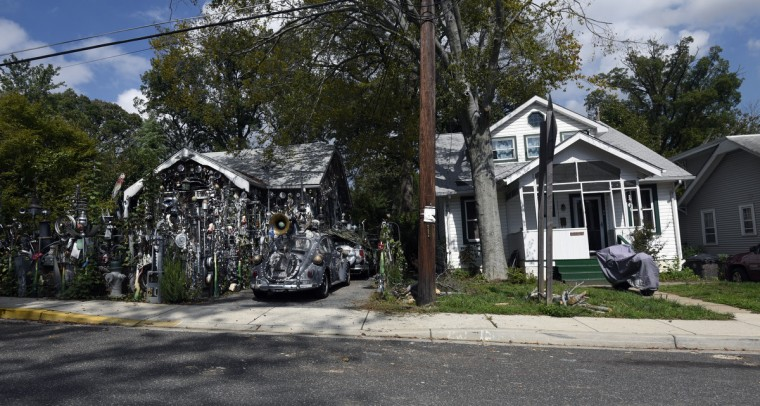 "Artist A. Clarke Bedford, creates  art made from found materials that he uses to adorn his cars and home. Bedford says ""The cars are part of the house the house is part of the cars. You can rearrange the cars to change the composition of the house.""    (Kim Hairston/Baltimore Sun)"