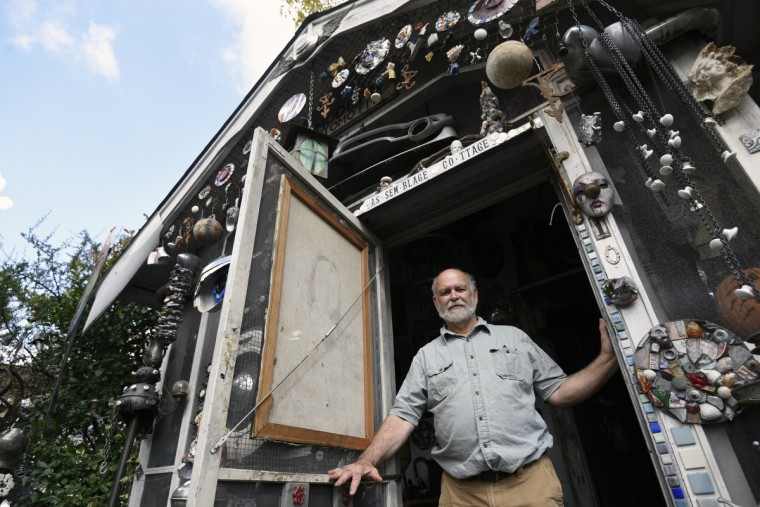 "Artist A. Clarke Bedford stands in the doorway of his ""As-sem-blage Co-ttage.""   (Kim Hairston/Baltimore Sun)"