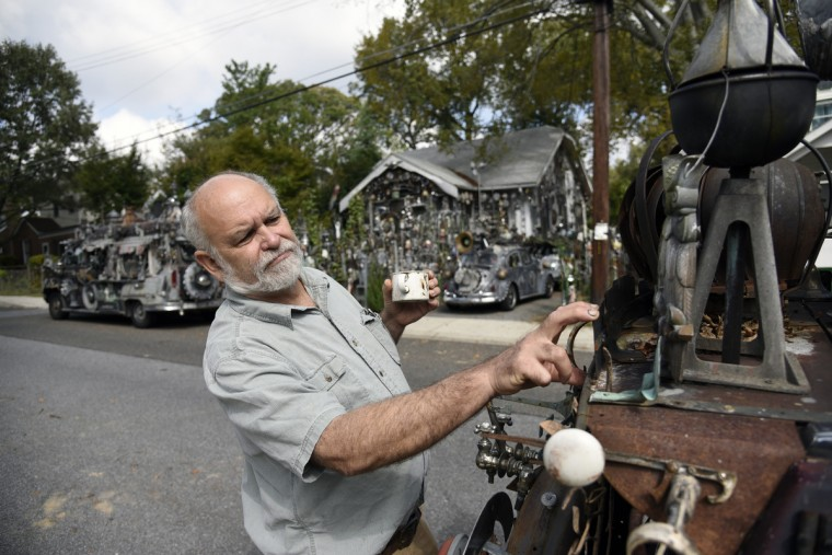 Artist A. Clarke Bedford checks one of his art cars parked across the street from his home. Bedford, a retired art conservator at the Hirshhorn Museum,  says he has always been interested in antiques and has incorporated images of the late 19th early 20th century into his work.  (Kim Hairston/Baltimore Sun)