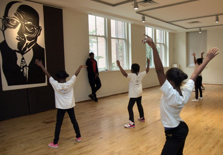 "Hip Hop teacher Tyone Pompey observes his Hip Hop class as students practice dance moves before a poster of American composer and Jazz legend James Hubert ""Eubie"" Blake. Children from ages 3 to 22 participate in the classes in African, ballet, creative movement, Hip Hop, modern, pre-dance, tap and jazz dance. The Studio offers both a community program and a professional training program for ages 8-21. (Algerina Perna/Baltimore Sun)"