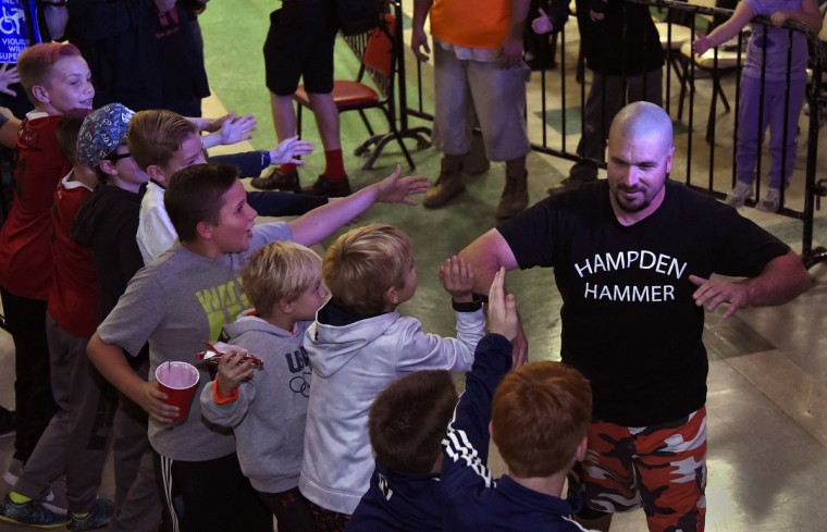"Wrestler Hampden Hammer, right, greets young fans on his way to the ring at the EWA ""Last Rites"" professional wrestling match that was held at Tall Cedars Hall. (Barbara Haddock Taylor/Baltimore Sun)"