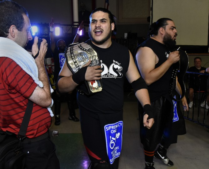 "Wrestlers TMHK (center) and Grizzly O, right, make their entrance at the EWA ""Last Rites"" professional wrestling match that was held at Tall Cedars Hall. (Barbara Haddock Taylor/Baltimore Sun)"