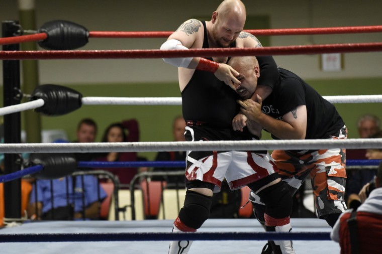 "Simon Ryme, left, and Hampden Hammer fight in the ring at the EWA ""Last Rites"" professional wrestling match that was held at Tall Cedars Hall. (Barbara Haddock Taylor/Baltimore Sun)"