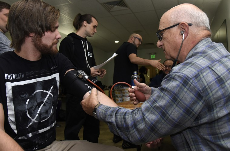 "Wrestler Jason Drake, left, gets a check-up from Dr. Ron Miller of Mt. Airy before his match at the EWA ""Last Rites"" professional wrestling match that was held at Tall Cedars Hall. (Barbara Haddock Taylor/Baltimore Sun)"