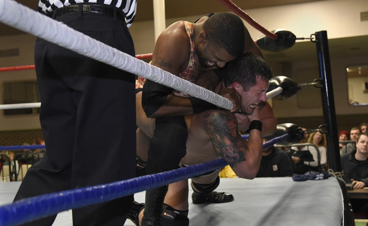 "Ivan Ali, left, and Joey Badami wrestle near the ropes in their match at the EWA ""Last Rites"" professional wrestling match that was held at Tall Cedars Hall. (Barbara Haddock Taylor/Baltimore Sun)"