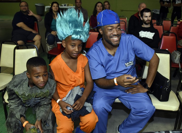 "Fans, dressed in Halloween costumes left to right: Jaden Holly, 11, Corie Fields, 10, and Phil Thompson, all of Owings Mills, watch the ""Last Rites"" EWA professional wrestling match that was held at Tall Cedars Hall. Jaden is Phil's son.  (Barbara Haddock Taylor/Baltimore Sun)"