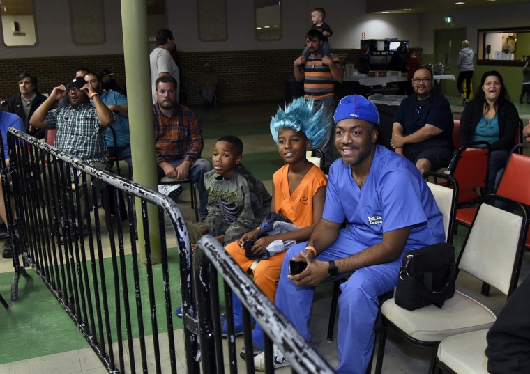 "Fans, dressed in Halloween costumes left to right front row:  Jaden Holly, 11, Corie Fields, 10, and Phil Thompson, all of Owings Mills, watch the ""Last Rites"" EWA professional wrestling match that was held at Tall Cedars Hall. Jaden is Phil's son.  (Barbara Haddock Taylor/Baltimore Sun)"