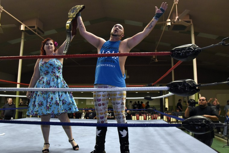 "Wrestler #Pat Athony, right, raises his arms in victory along with Violet, left, his social media ambassador, at the EWA  (Eastern Wrestling Association) ""Last Rites"" professional wrestling match that was held at Tall Cedars Hall. (Barbara Haddock Taylor/Baltimore Sun)"