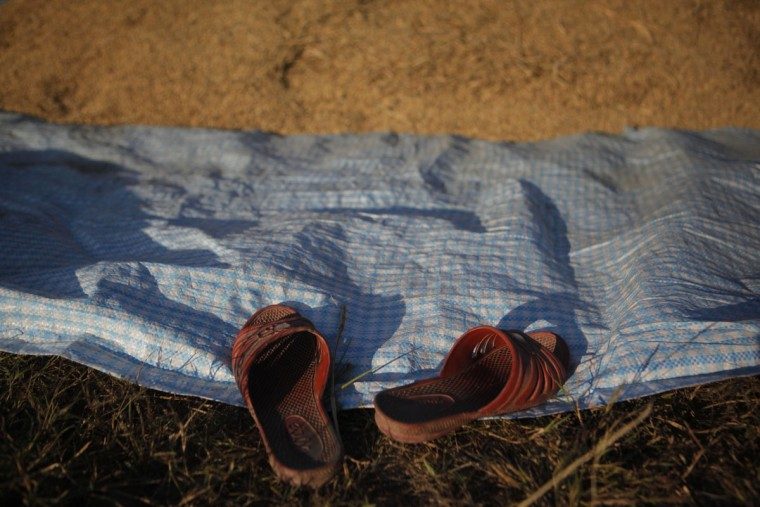 A flip flop of Nepalese farmer is seen as she separates grain from chaff a after harvest in Chunnikhel on the outskirts of Kathmandu, Nepal, Thursday, Oct. 20, 2016. Agriculture is the main source of food, income, and employment for the majority of people in Nepal. (AP Photo/Niranjan Shrestha)
