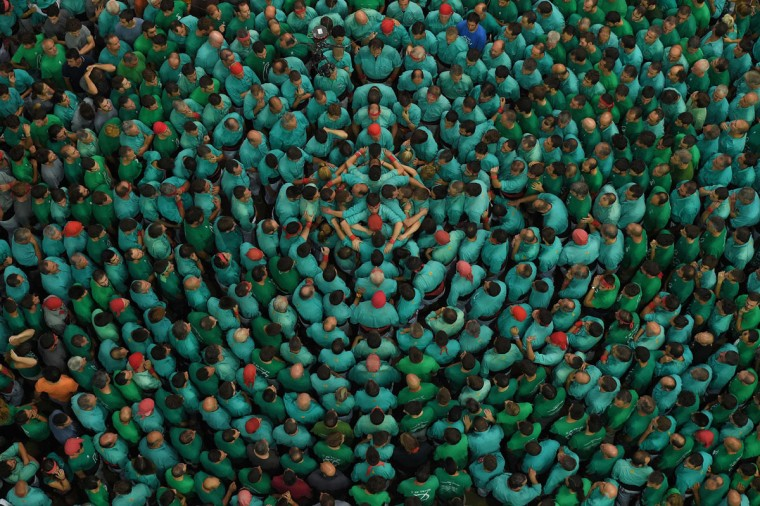 "Members of the ""Colla Jove Xiquets de Tarragona"" human tower team form a ""castell"" (human tower) during the XXVI human towers, or 'castells', competetion in Tarragona on October 2, 2016. These human towers, built traditionally in festivals within Catalonia, gather several teams that attempt to build and dismantle a human tower structure. (LLUIS GENE/AFP/Getty Images)"