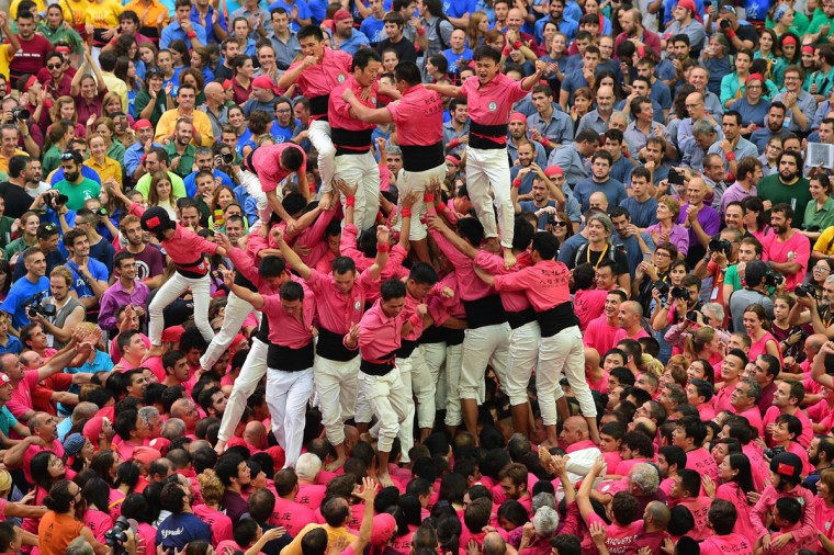 "Members of the Chinese ""Xiquets de Hangzhou"" human tower team celebrate after forming a ""castell"" during the XXVI human towers, or castells, competetion in Tarragona on October 1, 2016. These human towers, built traditionally in festivals within Catalonia, gather several teams that attempt to build and dismantle a tower structure. (LLUIS GENE/AFP/Getty Images)"