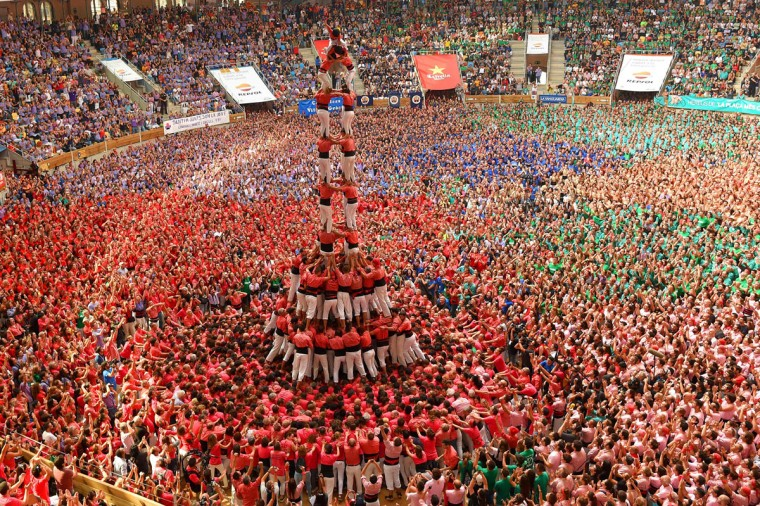 "Members of the ""Colla Vella dels Xiquets de Valls"" human tower team form a ""castell"" (human tower) during the XXVI human towers, or 'castells', competetion in Tarragona on October 2, 2016. These human towers, built traditionally in festivals within Catalonia, gather several teams that attempt to build and dismantle a human tower structure. (LLUIS GENE/AFP/Getty Images)"
