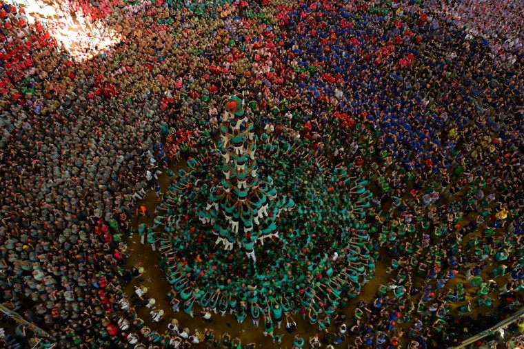 "Members of the ""Castellers de Vilafranca"" human tower team form a ""castell"" (human tower) during the XXVI human towers, or 'castells', competetion in Tarragona on October 2, 2016. These human towers, built traditionally in festivals within Catalonia, gather several teams that attempt to build and dismantle a human tower structure. (LLUIS GENE/AFP/Getty Images)"