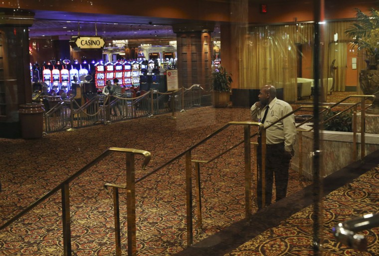 A security guard looks on as a few people stand near slot machines at the Trump Taj Mahal, early Monday, Oct. 10, 2016, in Atlantic City, N.J. The sprawling Boardwalk casino, with its soaring domes, minarets and towers built to mimic the famed Indian palace, shut down at 5:59 a.m., Monday, Oct. 10, 2016, having failed to reach a deal with its union workers to restore health care and pension benefits that were taken away from them in bankruptcy court. (AP Photo/Mel Evans)