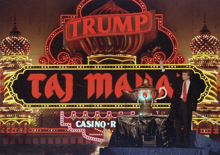 "In this April 5, 1990 file photo, Donald Trump stands next to a genie's lamp as the lights of his Trump Taj Mahal Casino Resort light up during ceremonies to mark its opening in Atlantic City, N.J. Trump opened his Trump Taj Mahal casino 26 years ago, calling it ""the eighth wonder of the world."" But his friend and fellow billionaire Carl Icahn is closing it Monday morning, making it the fifth casualty of Atlantic City's casino crisis. (AP Photo/Mike Derer, File)"