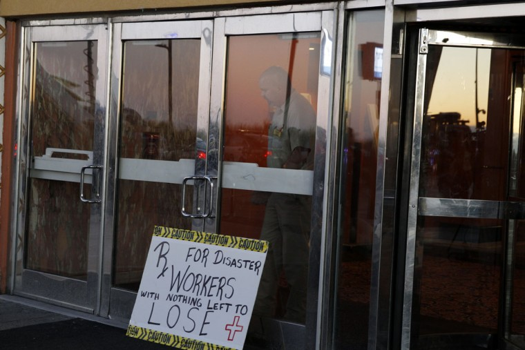 A worker locks the doors from opening to block the entrance as the Trump Taj Mahal closes early Monday, Oct. 10, 2016, in Atlantic City, N.J. The sprawling Boardwalk casino, with its soaring domes, minarets and towers built to mimic the famed Indian palace, shut down at 5:59 a.m., having failed to reach a deal with its union workers to restore health care and pension benefits that were taken away from them in bankruptcy court. (AP Photo/Mel Evans)