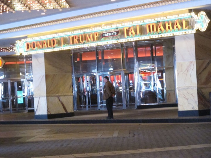 In this May 17, 2016 photo, a man waits at the main entrance to the Trump Taj Mahal casino in Atlantic City, N.J.  Donald Trump, built the casino in 1990, but lost control of it in a bankruptcy last decade. Trump, the Republican presidential nominee, told The Associated Press he will insist that his name be removed from the entire casino once it closes on Monday Oct. 10, 2016. The sign with his name on it above the entrance had been removed at least a week before the casino was to shut down. (AP Photo/Wayne Parry)