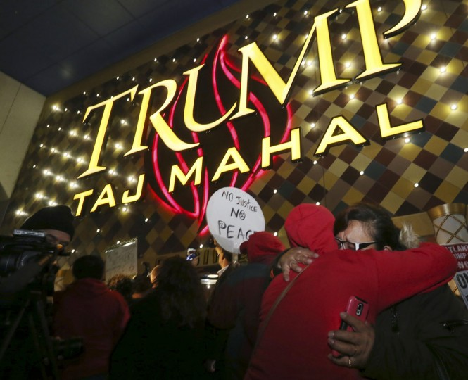 Former employees hug early in the morning outside the closing Trump Taj Mahal, Monday, Oct. 10, 2016, in Atlantic City, N.J. The sprawling Boardwalk casino, with its soaring domes, minarets and towers built to mimic the famed Indian palace, shut down at 5:59 a.m., having failed to reach a deal with its union workers to restore health care and pension benefits that were taken away from them in bankruptcy court. (AP Photo/Mel Evans)