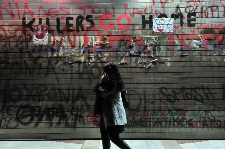 A woman walks past graffiti outside of the US consulate during a demonstration against the visit of the US president in Thessaloniki on November 15, 2016. US President Barack Obama flew into Athens on his final foreign trip to Europe, seeking to calm the nerves of allies concerned by Donald Trump's shock presidential election victory. (Sakis Mitrolidis/AFP/Getty Images)