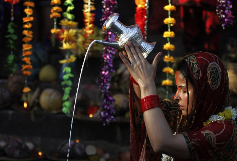 A Nepalese woman pours milk as she offers prayers to the setting Sun on the banks of the Bagmati River during the Chhath Puja festival in Kathmandu, Nepal, Sunday, Nov. 6, 2016. During Chhath, an ancient Hindu festival, rituals are performed to thank the Sun God for sustaining life on earth. (AP Photo/Niranjan Shrestha)