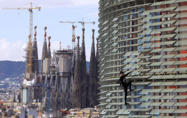 "French urban climber, Alain Robert, also known as ""French Spiderman"", scales the 475 feet of the Agbar tower in Barcelona, Spain, Friday, Nov. 25, 2016. (AP Photo/Manu Fernandez)"