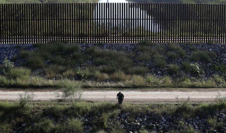 In this Wednesday, Nov. 16, 2016, photo, a U.S. Customs and Border Patrol agent searches for suspected illegal immigrants passing through the area in Hidalgo, Texas. The idea of a concrete wall spanning the entire 1,954-mile southwest frontier collides head-on with multiple realities, like a looping Rio Grande, fierce local resistance, and cost. (AP Photo/Eric Gay)