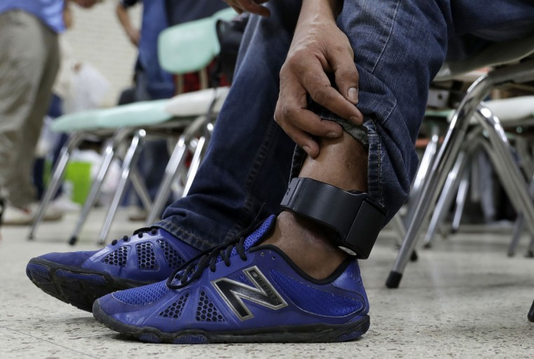 In this Sunday, Nov. 13, 2016, photo, Luis Carlos, a construction worker from Honduras who is headed to Miami with his son, wears an ankle monitor as he sits at the Sacred Heart Community Center in the Rio Grande Valley border city of McAllen, Texas after he was released after processing by U.S. Customs and Border Patrol. (AP Photo/Eric Gay)