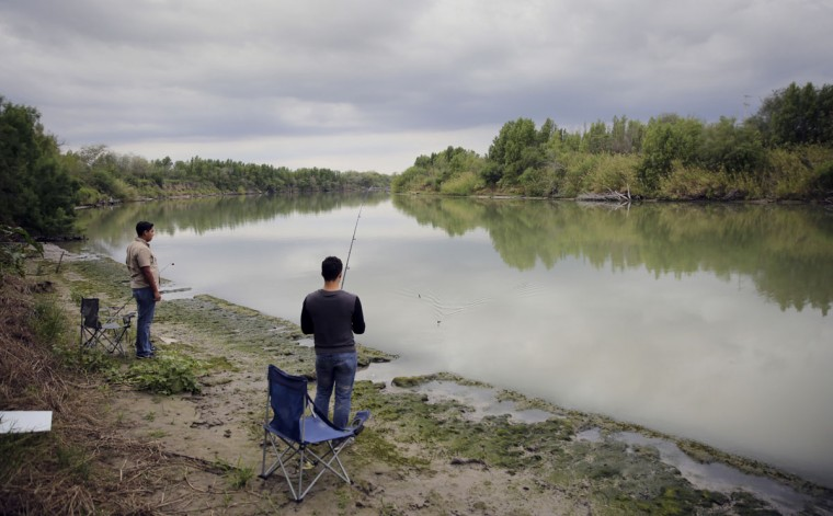 In this Saturday, Nov. 12, 2016, photo, Isaac Aguilar, left, and Isac Ramos, right, fishe at a ranch on the banks of the Rio Grande in Los Ebanos, Texas. The area would be cut of if a border wall is build in the area. (AP Photo/Eric Gay)