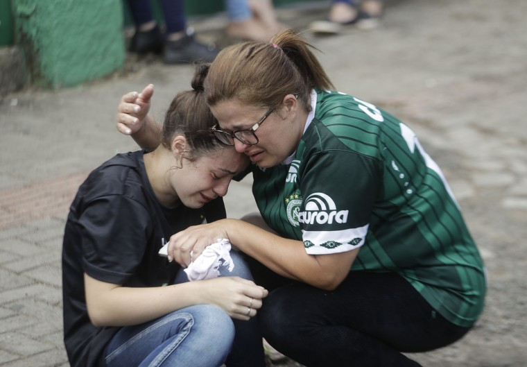 Fans of Brazil's soccer team Chapecoense mourn outside the Arena Conda stadium in Chapeco, Brazil, Tuesday, Nov. 29, 2016. A chartered plane that was carrying the Brazilian soccer team to the biggest match of its history crashed into a Colombian hillside and broke into pieces, Colombian officials said Tuesday. (AP Photo/Andre Penner)