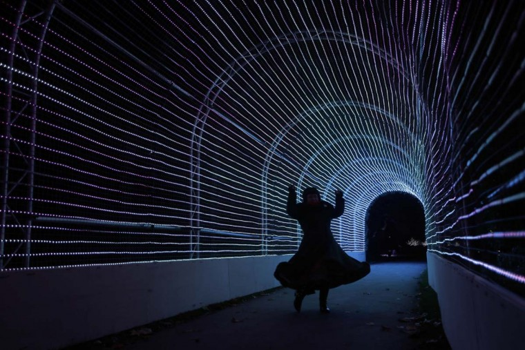 "A representative poses for photographs inside a tunnel of lights made up of 63,000 LEDs at the launch of ""Christmas at Kew"" at the Kew Royal Botanic Gardens in London, Tuesday, Nov. 22, 2016. The event is open to the public from November 23 until January 2 and includes an illuminated trail lit up by over 60,000 lights. (AP Photo/Matt Dunham)"