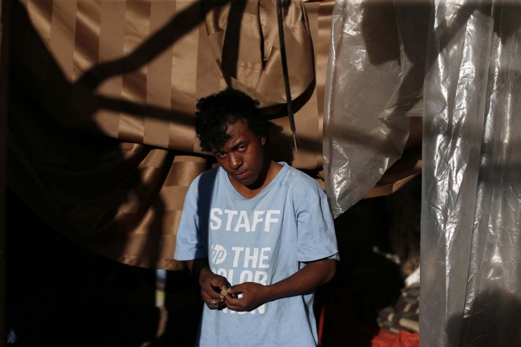 In this Oct. 10, 2016 photo, Dani, 19, poses for a picture outside his sleeping space, inside an abandoned ruined building in Santiago, Chile. Dani is part of a group of teens that lives in the streets of Santiago, surviving by begging and petty crime. (AP Photo/Luis Hidalgo)
