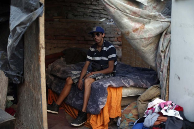 In this Oct. 10, 2016 photo, 21-year-old Julio, 21, poses for a photo in his sleeping space inside a ruined and abandoned building were he lives with other youths, in Santiago, Chile. Julio was once a ward of Chile's National Service for Minors but he walked out and now lives in the the streets. President Michelle Bachelet has committed $ 3.7 million for an overhaul of the agency charged with looking after more than 100,000 children in the government's care each year in Chile, some in their own homes and some in shelters. (AP Photo/Luis Hidalgo)