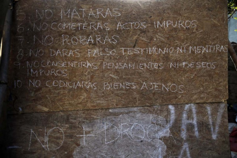 """In this Oct. 10, 2016 photo, the ten commandments are displayed on a piece of plywood, with the extra """"No More Drugs,"""" added at the bottom, in a ruined abandoned building used by street children for shelter, in Santiago, Chile. Many if not all of the youths living in the ruin were once wards of the state, living in shelters of National Service for Minors. (AP Photo/Luis Hidalgo)"""