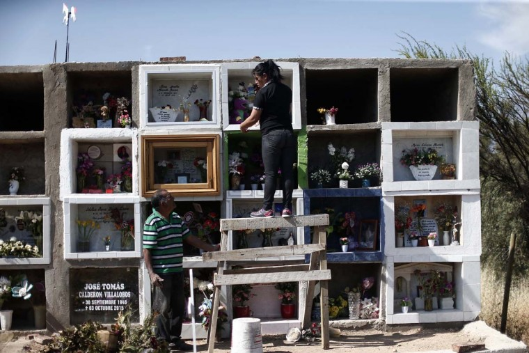 In this Oct. 22, 2016 photo, Juana Poblete, the mother Lissette, a young girl that died while under the care of the state, cleans her daughter's tomb in Til Til, Chile. Poblete had sent her daughter to a government shelter hoping authorities could protect her as she became increasingly violent and difficult to handle. (AP Photo/Luis Hidalgo).