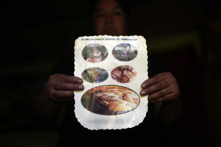 In this Oct. 22, 2016 photo, Juana Poblete, poses with photos of her daughter, Lissette who died under the care of the Chilean state, in Til Til, Chile. Lissette's case exploded in a crisis over the care of at-risk children that has outraged Chileans. After initially reporting just 185 deaths, the government recently acknowledged that 865 children have died under the care of the National Service for Minors over 11 years. (AP Photo/Luis Hidalgo).
