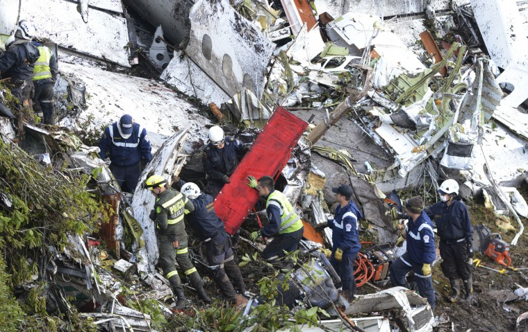 Rescue workers comb through the wreckage site of an airplane crash, in La Union, a mountainous area near Medellin, Colombia, Tuesday , Nov. 29, 2016. The chartered plane was carrying a Brazilian soccer team to the biggest match of its history when it crashed into a Colombian hillside and broke into pieces, killing 75 people and leaving six survivors, Colombian officials said Tuesday. (AP Photo/Fernando Vergara)