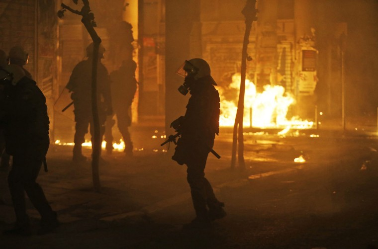 Fire bombs are thrown by demonstrators towards riot police officers, during clashes following a protest against the visit of US President Barack Obama in Athens, Tuesday, Nov. 15, 2016. Greek riot police used tear gas and stun grenades in central Athens Tuesday to disperse about 3,000 left-wing marchers after they tried to enter an area declared off-limits to demonstrators. (AP Photo/Lefteris Pitarakis)
