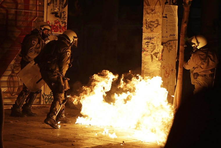 Police officers look at flames from a fire bomb thrown by demonstrators during a protest against the visit of US President Barack Obama in Athens, Tuesday, Nov. 15, 2016. Greek riot police used tear gas and stun grenades in central Athens Tuesday to disperse about 3,000 left-wing marchers protesting a visit by President Barack Obama, after they tried to enter an area declared off-limits to demonstrators. (AP Photo/Thanassis Stavrakis)