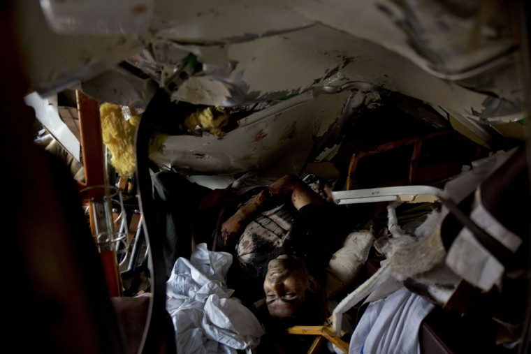 A victim's body is trapped amid the debris after 14 coaches of an overnight passenger train rolled off the track near Pukhrayan village Kanpur Dehat district, Uttar Pradesh state, India, Sunday, Nov. 20, 2016. Dozens were killed and dozens more were injured in the accident. (AP Photo/Rajesh Kumar Singh)