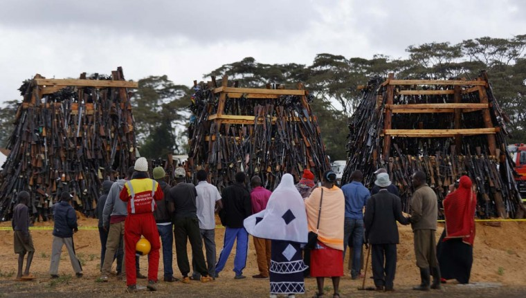 People watch before a pile of 5,250 illegal weapons are burned by Kenyan police in Ngong, near Nairobi, in Kenya Tuesday, Nov. 15, 2016. The weapons consisted of both confiscated and surrendered firearms that had been stockpiled over almost a decade and were destroyed by police as a message to the public to surrender others. (AP Photo/Ben Curtis)