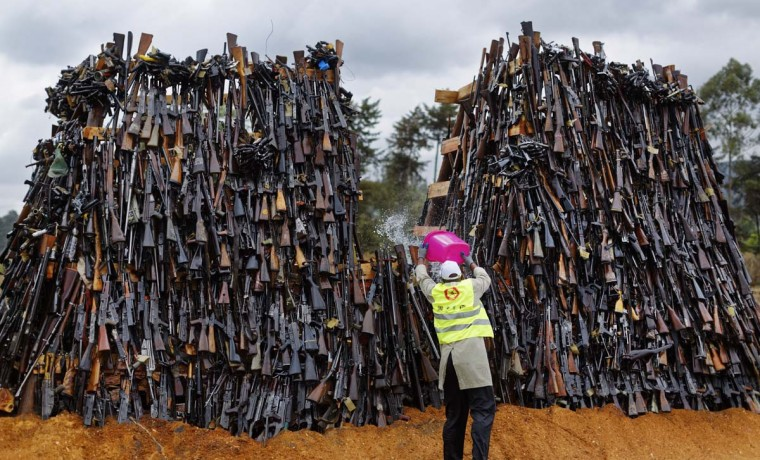 A man pours fuel on a pile of 5,250 illegal weapons before they were burned by Kenyan police in Ngong, near Nairobi, in Kenya Tuesday, Nov. 15, 2016. The weapons consisted of both confiscated and surrendered firearms that had been stockpiled over almost a decade and were destroyed by police as a message to the public to surrender others. (AP Photo/Ben Curtis)