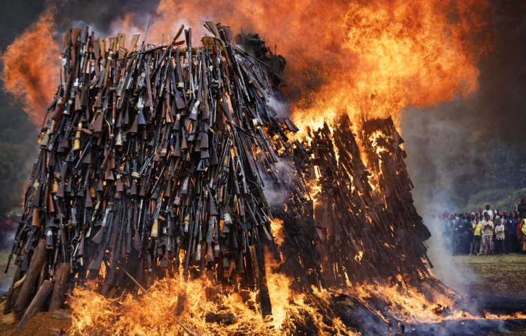 A pile of 5,250 illegal weapons are burned by Kenyan police in Ngong, near Nairobi, in Kenya Tuesday, Nov. 15, 2016. The weapons consisted of both confiscated and surrendered firearms that had been stockpiled over almost a decade and were destroyed by police as a message to the public to surrender others. (AP Photo/Ben Curtis)