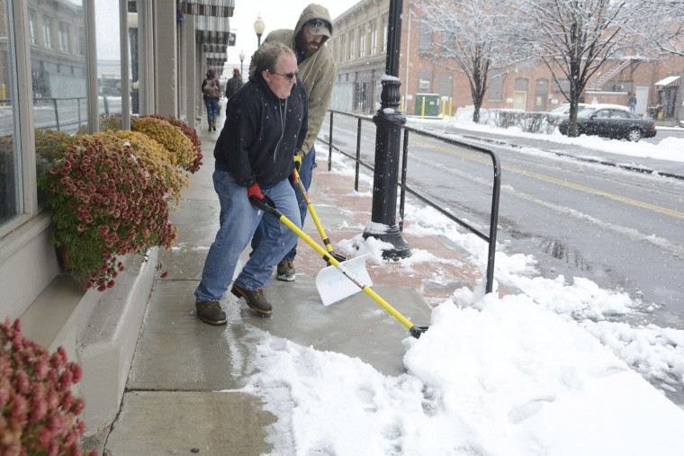 In this Sunday, Nov. 20, 2016, photo, Mark LaPier and Jeremy LaPier work in tandem as they shovel heavy snow from the sidewalks along Holden Street in North Adams, Mass., following a winter storm. (Gillian Jones/The Berkshire Eagle via AP)