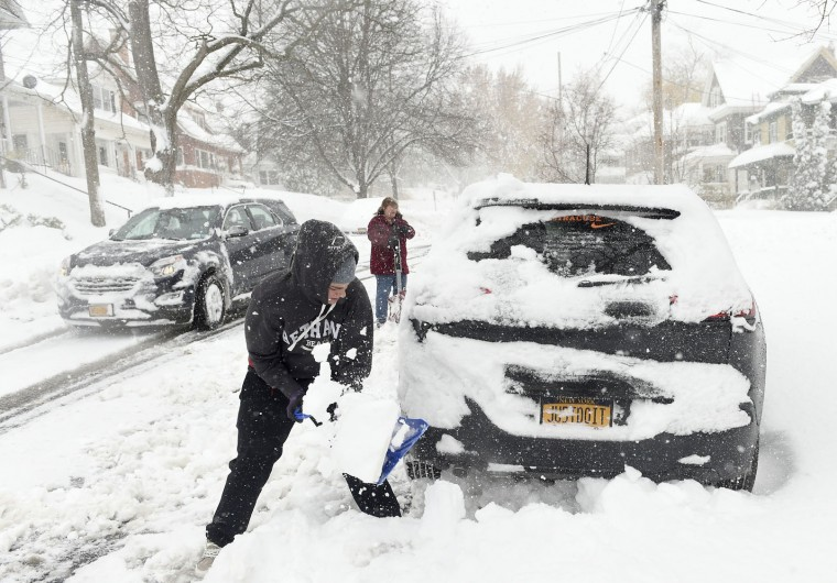 People dig out plowed-in cars in Syracuse, NY., Monday, Nov.21, 2016, after Syracuse's first snowstorm of the season belted the area. At least ten inches covered the area along with high winds. (Dennis Nett/The Syracuse Newspapers via AP)